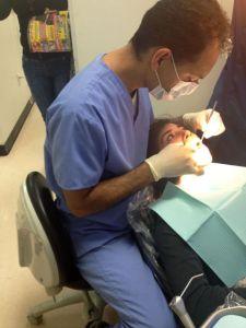 Dentist David Rabizadeh perfora una limpieza regular en su paciente en Boyle Heights. Photo by Emily Valdez