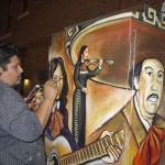 Raul Gonzalez paints a mural on First Street and Boyle Avenue in Boyle Heights.