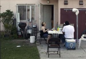 Una familia de Ramona Gardens arregla la cena afuera de su hogar. Foto de Jonathan Olivares