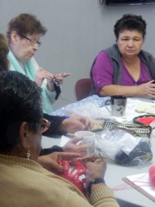 Seniors knit together at the Senior Club in Ramona Gardens. Photo by Marcia Facundo