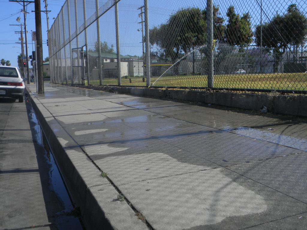 Sprinklers at Pico Aliso Recreation Center soak the field as well as sidewalks outside the fence. Photo by Jessica Perez