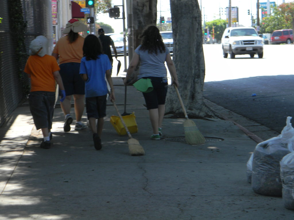 Fed up with the trash problem, community residents do their part to clean up their neighborhood. Photo by Dulce Morales