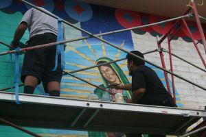 Mural restorers work on the Gudalupana in Ramona Gardens. Photo by Antonio Mejias.