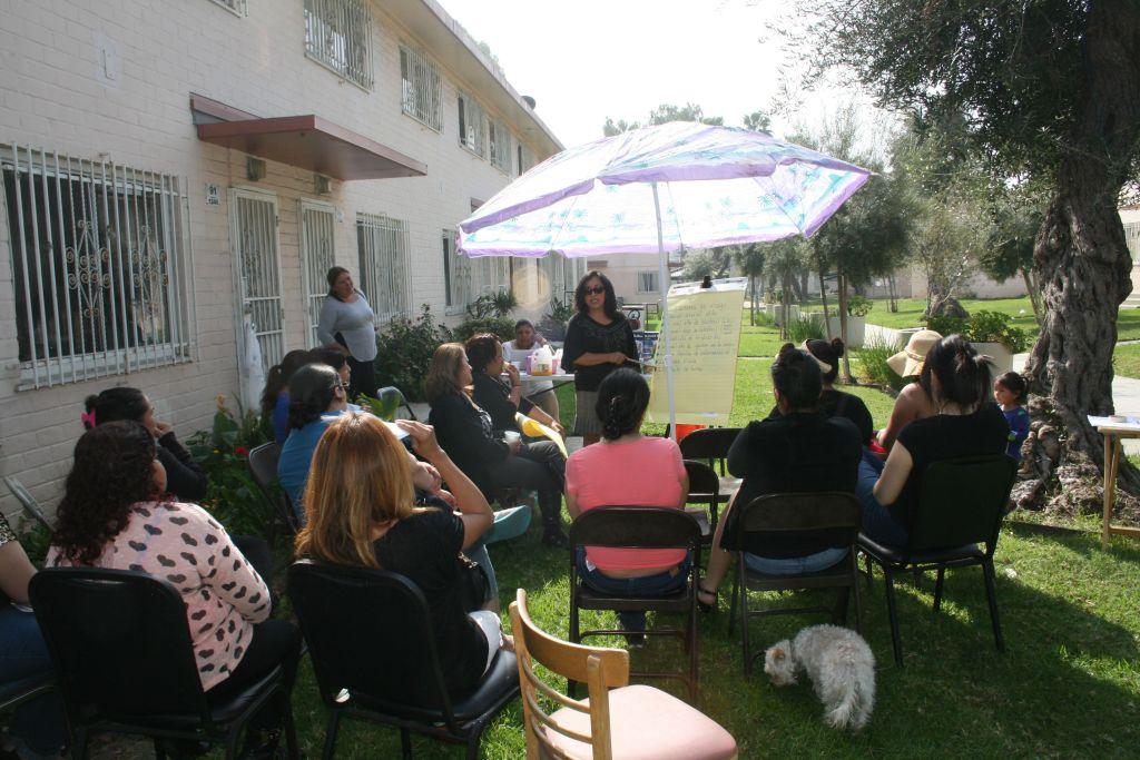 Promotora Mari Ruiz teaches a class on hypertension to Ramona Gardens residents as lead promotora Martha González observes (left, background). Photo by Antonio Mejias