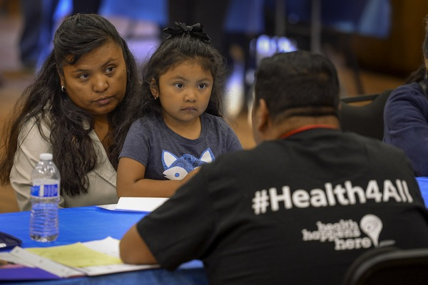 Sarai Espinoza and daughter Alexa Ordonez sit patiently as paper work is filled out by an enrollment volunteer during the Amate y Asegurate health care program screening. (USC Photo/Gus Ruelas)