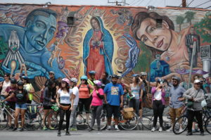 Erik Huerta and Maryann Aguirre, two of the organizers of the Eastside Mural Ride, spoke about the history of several murals in Boyle Heights and East Los Angeles. Photo by Erik Sarni