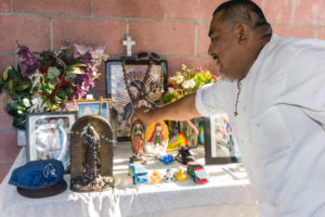 Juan Méndez points to one of the photos in his home's altar to his son José. Photo by Ernesto Orozco