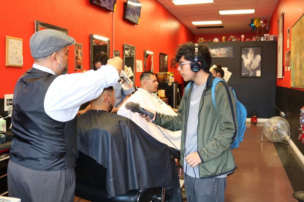 Boyle Heights student Alex Medina interviews owner and customer at The Cream Shop barberhop in Boyle Heights.
